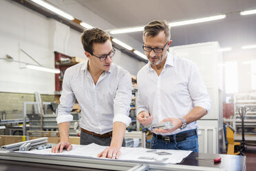 Two businessmen in factory discussing plan - DIGF03348