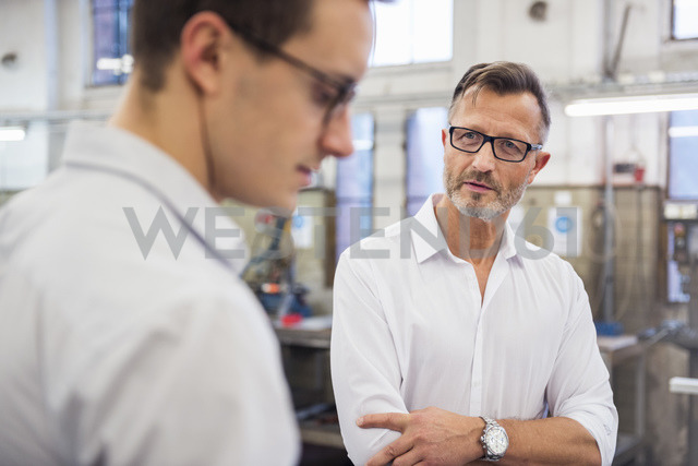Two businessmen discussing in factory - DIGF03354
