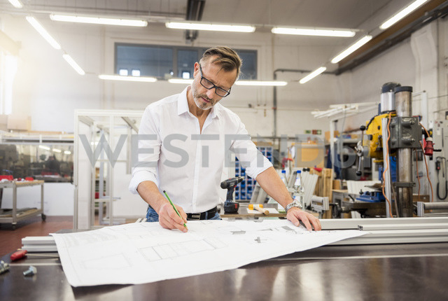 Mature businessman in factory working on plan - DIGF03357