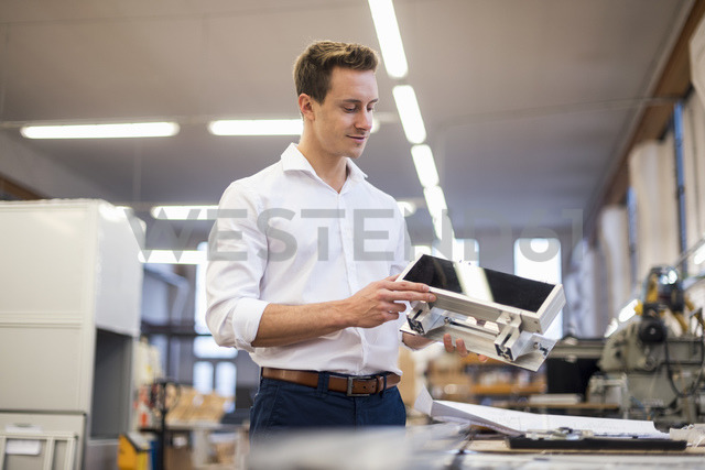 Smiling young businessman in factory holding component - DIGF03360