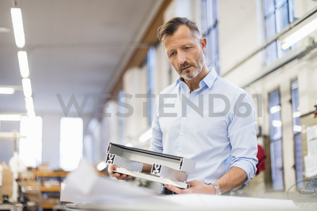 Mature businessman in factory examining component - DIGF03363