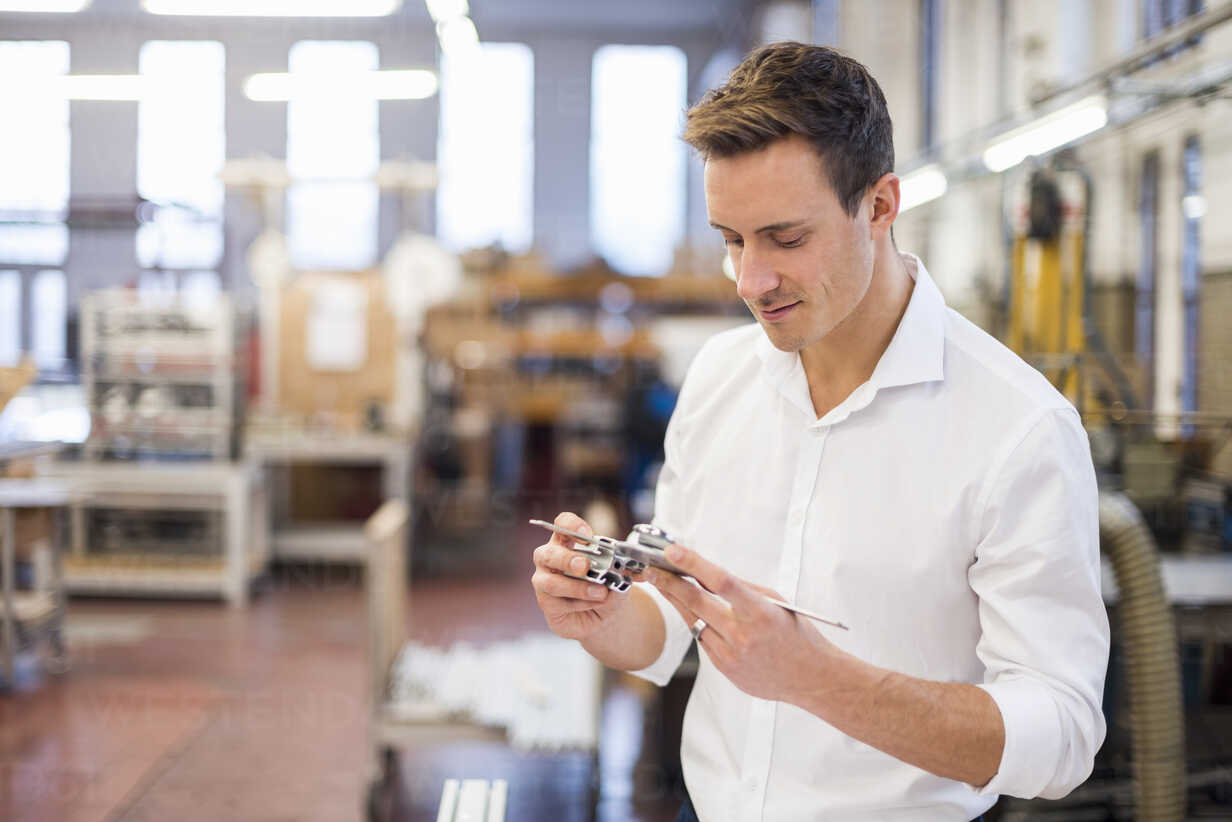 Young businessman in factory holding component - DIGF03366 - Daniel Ingold/Westend61