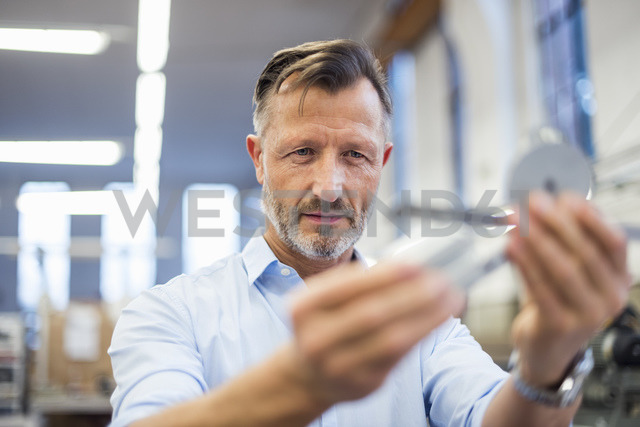 Mature businessman in factory examining component - DIGF03369