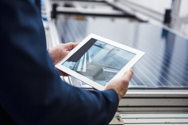 Businessman in solar factory holding tablet - DIGF03381