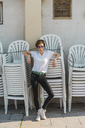 Woman wearing sunglasses standing in front of stackes chairs - AFVF00094