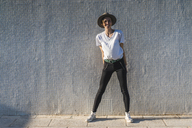Laughing woman wearing hat standing in front of tiled wall at sunlight - AFVF00100