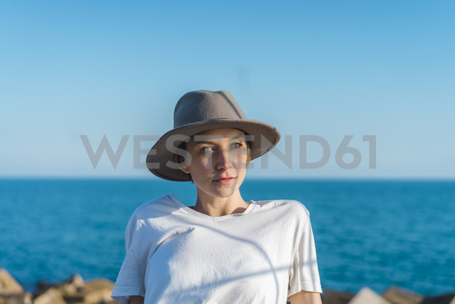 Portrait of woman wearing hat in front of the sea - AFVF00109