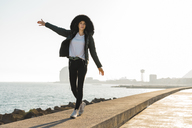 Spain, Barcelona, woman wearing hooded jacket balancing on promenade - AFVF00112