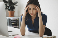 Young businesswoman suffering from headache at desk in office - FSIF01376