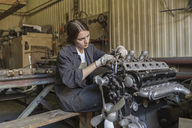 Female mechanic repairing car engine at garage - FSIF01412