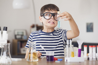Cross eyed boy looking at test tube during science experiment in house - FSIF01424