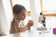 Curious girl looking at specimen with microscope on table at home - FSIF01433