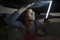 Mechanic holding illuminated fluorescent light while examining car - FSIF01466