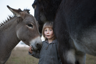 Portrait of cute girl standing with donkeys on field - FSIF01475