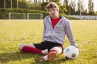 Portrait of young soccer player resting on field - FSIF01496