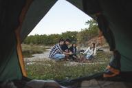 Friends roasting marshmallows seen from tent - FSIF01523