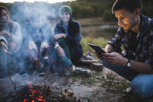 Young man using digital tablet while sitting with friends by bonfire - FSIF01526