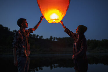 Man and woman releasing paper lanterns at lakeshore - FSIF01529