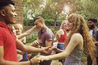 Cheerful friends dancing at yard during party - FSIF01541
