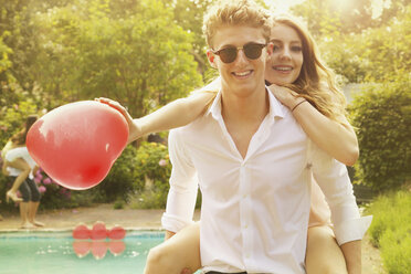 Portrait of happy man piggybacking woman holding heart shape balloon at poolside - FSIF01544