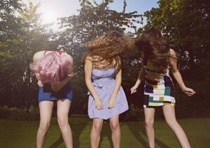 Excited female friends tossing hair at yard during sunny day - FSIF01547