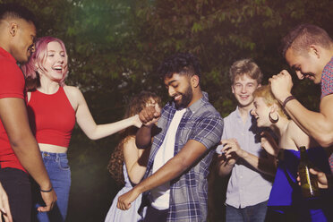 Cheerful multi-ethnic friends dancing at yard during party - FSIF01550