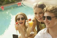 Cheerful woman holding drinks while sitting with male friend at poolside - FSIF01556