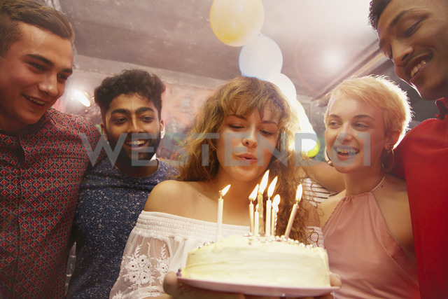 Woman blowing candles while celebrating birthday with friends at yard - FSIF01559