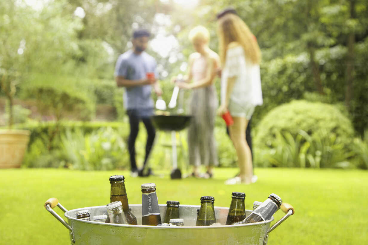 Beer bottles in bucket while friends enjoying barbecue party in background at yard - FSIF01562 - fStop/Westend61
