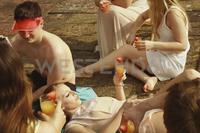 High angle view of friends holding drinks while relaxing at poolside - FSIF01574