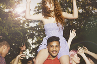 Man carrying female friends while enjoying party at yard - FSIF01577