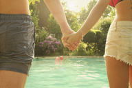 Rear view midsection of young man and woman holding hands while standing by swimming pool - FSIF01583