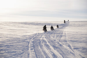People driving snowmobiles on field against sky during winter - FSIF01586
