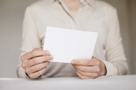 Midsection of mid adult woman holding a blank card - FSIF01607