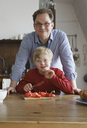 Portrait of father and boy at table in kitchen - FSIF01640