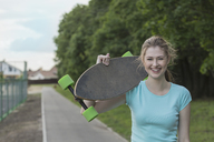 Portrait of cheerful woman holding skateboard standing on footpath at park - FSIF01652