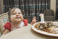 Cute girl with messy face having birthday cake at table - FSIF01658
