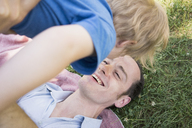 High angle view of cheerful father lifting son in park - FSIF01664