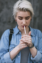 Young fashionable woman smoking cigarette while standing outdoors - FSIF01676