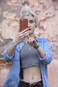 Confident young woman taking selfie through smart phone while standing against wall - FSIF01679