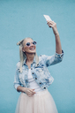 Happy fashionable young woman talking selfie against blue wall - FSIF01685