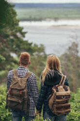 Rear view of couple wearing backpack standing in forest - FSIF01694