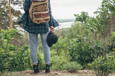 Low section of female backpacker holding hat while standing at forest - FSIF01697