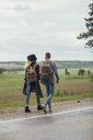 Couple walking on roadside by field against sky - FSIF01703