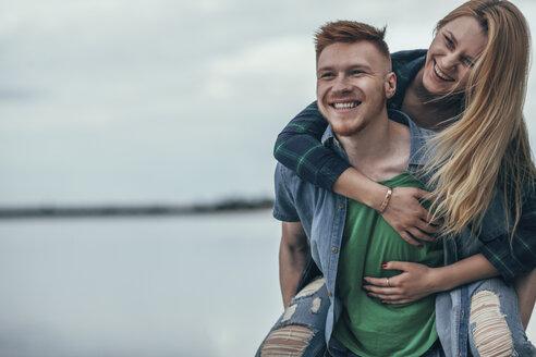 Happy man piggybacking cheerful girlfriend on lakeshore against sky - FSIF01709