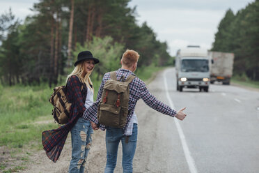 Happy couple hitchhiking on roadside at forest - FSIF01712