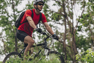 Confident man riding mountain bike in forest - FSIF01724