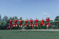 Happy soccer team cheering on field against sky - FSIF01742