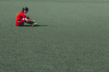 Side view of soccer player sitting on playing field - FSIF01748