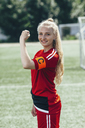 Confident soccer captain showing band with letter C on field - FSIF01751